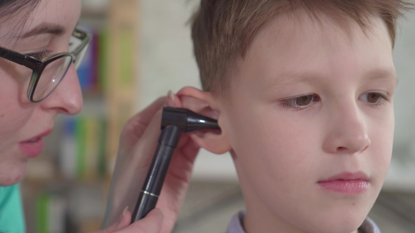 An otolaryngologist examines the ears of a little boy close up