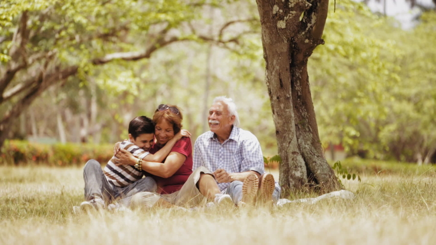 Old people, senior couple, elderly man and woman, husband and wife in park, active seniors, retirement age. Outdoor family fun. Happy grandpa and grandma hugging boy, child, kid at picnic. Slow motion