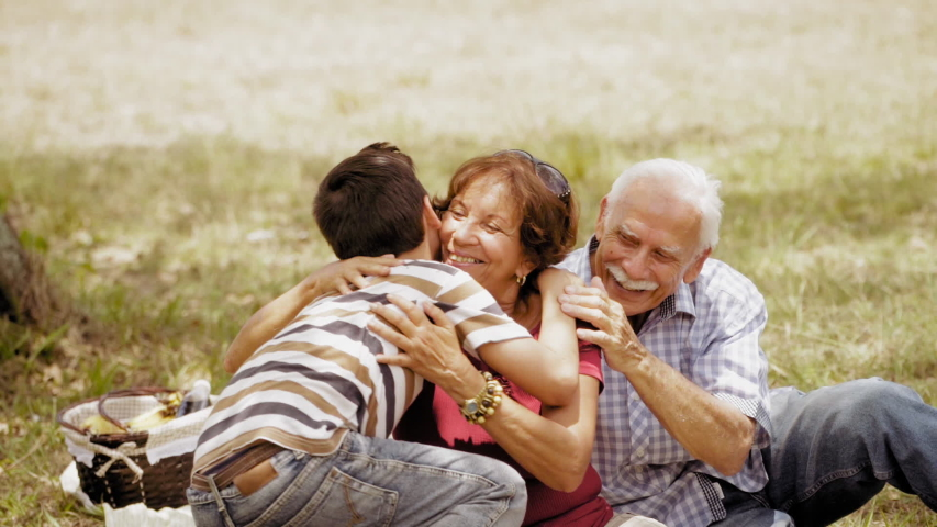 Old people, senior couple, elderly man and woman, husband and wife in park. Outdoors activity, leisure, family recreation. Happy grandfather and grandmother hug grandson, boy, child. Slow motion  Royalty-Free Stock Footage #1042616875