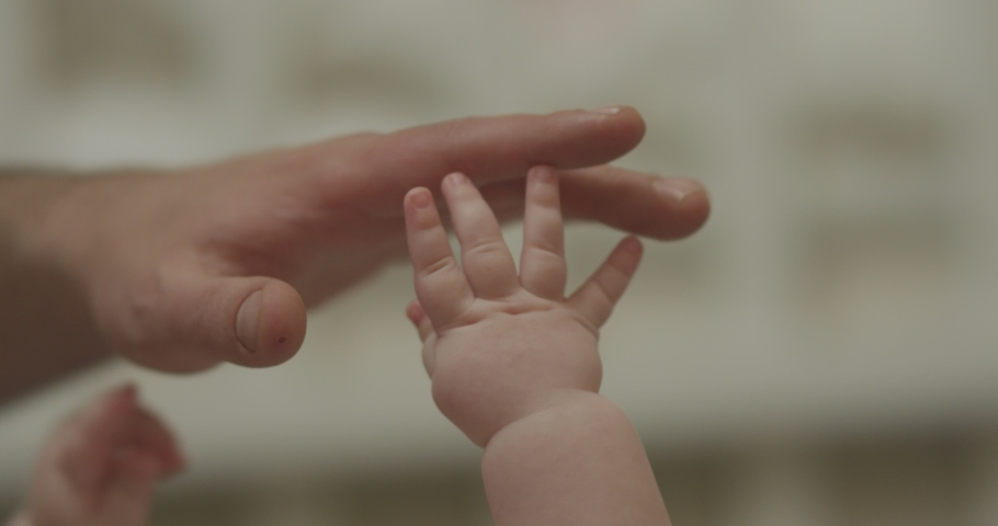 4K Closeup shot of baby's little cute hand reaching for father's loving finger . Baby holding parent's finger. Parent holding newborns hand in Slow Motion. Hand in hand. Father and newborn baby .