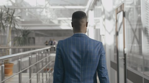 Back view successful of african-american businessman walking in business center after corporate meeting