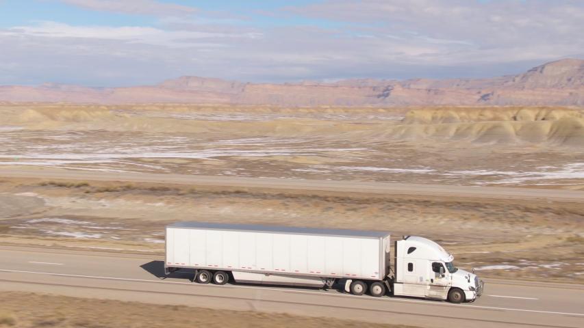 AERIAL: Semi-trailer truck speeds along the motorway running across the desert in Utah. Wintry desert landscape surrounds truck driving down the interstate highway running across rugged US wilderness.