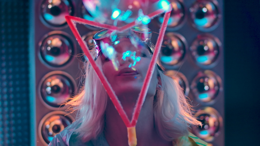 Happy 30s Woman Closeup. Portrait Of Confident And Attractive Young One Woman Smiling Carefree Having Fun Blowing Looking At Camera. Joy Girl Enjoying Holidays Merry Christmas in Colorful Light Neon