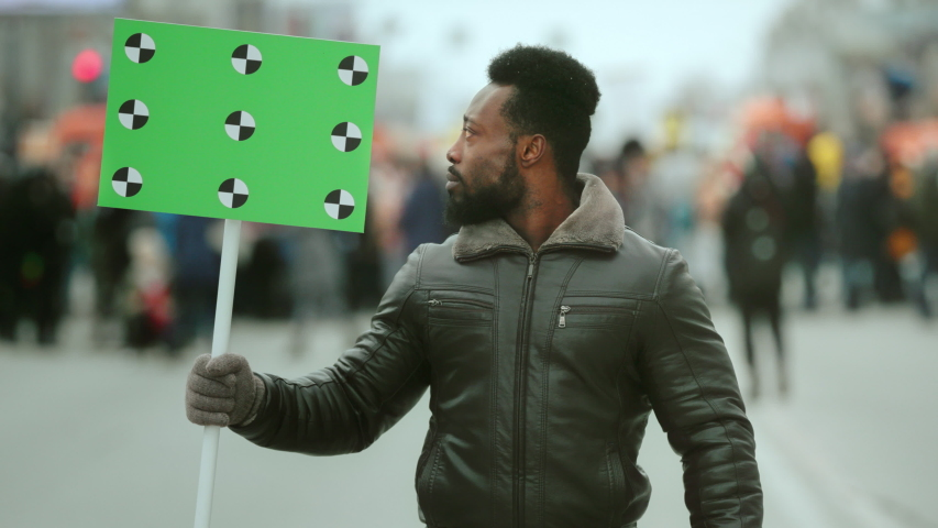 African american man hold banner in hand. Tracking points. Copy space. Blank green screen board. Crowd people demonstration. Afro man looking at camera. Revolution city street. Political rally fight. | Shutterstock HD Video #1042638679