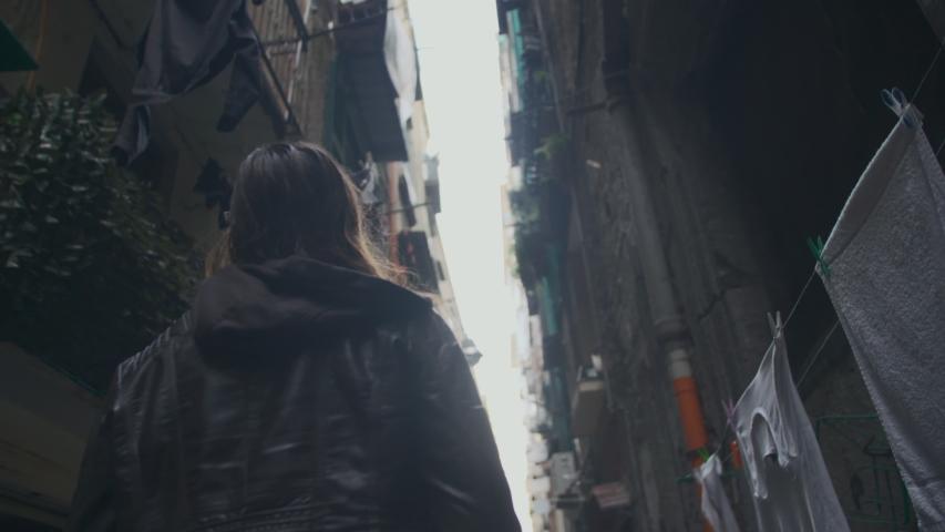 Brown haired girl walks between tall decrepit buildings in an unlit alleyway in Europe. Young woman in her thirties walking alone in an old neighborhood alleyway. Slow-motion, back view, side view.