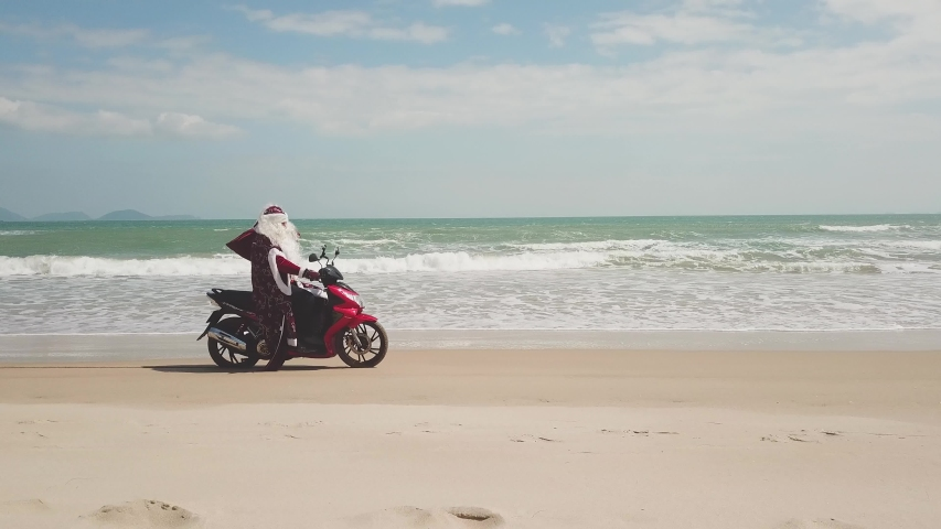 Santa Claus on the seashore rides a bike with a bag of gifts. | Shutterstock HD Video #1042680649