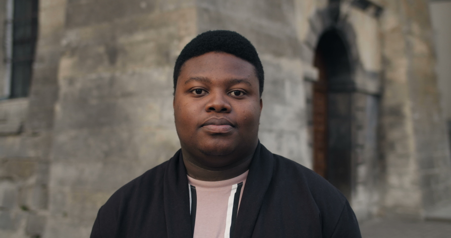 Close up of happy fat man looking to camera. Young african guy standing outdoors and smiling. Portraits. Daylight. Concept of people and emotions. Old buildings background Royalty-Free Stock Footage #1042686346