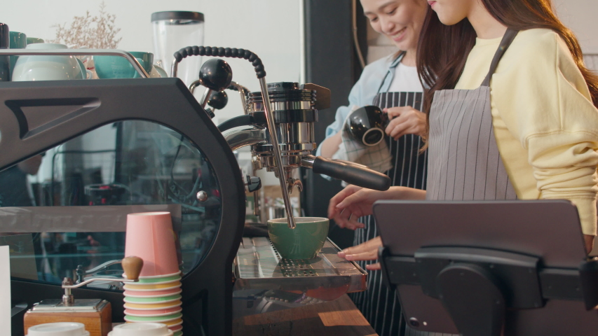 Beautiful young Asia lady barista working with coffee machine in coffee shop. Two small business owner Korean girl in apron making coffee by coffee machine with friend at counter in urban cafe. | Shutterstock HD Video #1042687090