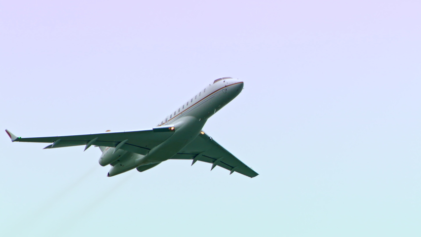 Private business jet flying in the sky. No logos or markings. Isolated on the airplane as it flies over the camera. Royalty-Free Stock Footage #1042689742