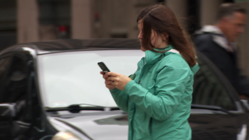 BOSTON, MA - circa 2019: Woman crossing a busy city street while looking at cell phone and texting | Shutterstock HD Video #1042689790