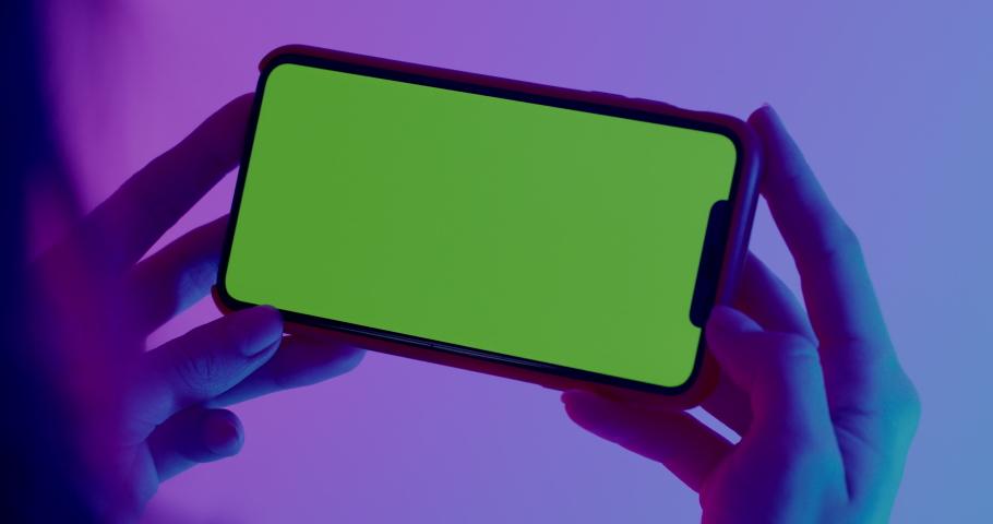 MINSK/BELARUS - CIRCA 2019: GREEN SCREEN CU Caucasian female using Apple iPhone XS Max, horizontal orientation, colorful neon background. 4K UHD RAW Graded footage