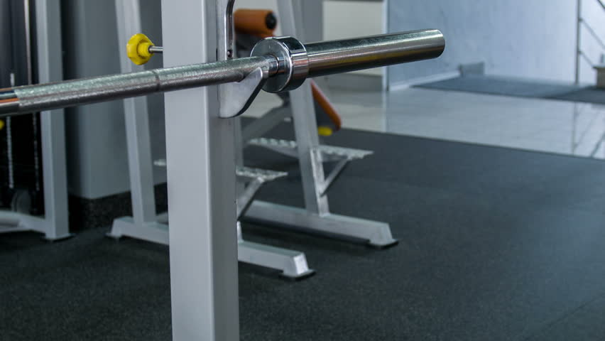 Fit healthy athlete is hanging heavy yellow weight on barbell. He is smiling and looking at the camera confidently | Shutterstock HD Video #10426949