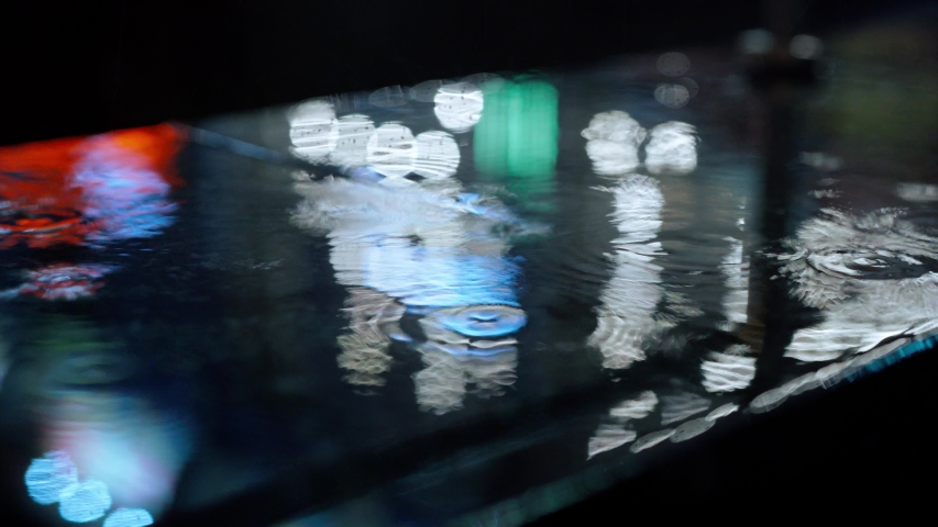 Closeup Rain drops Falling On puddle with lights reflection on city sidewalk. Rain Drop With Street Lights and colorful traffic lights At Night Blur Bokeh Abstract 4k stock footage