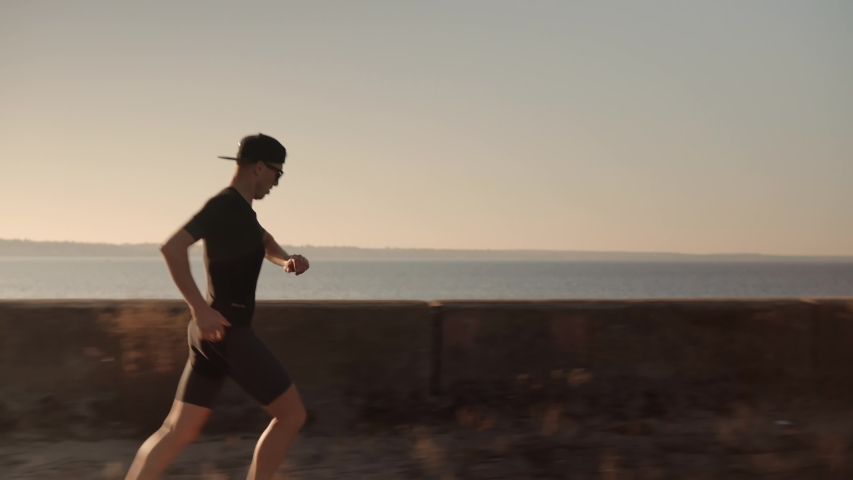 Running Man Workout And Checking Pulse.Runner Man In Sportswear Exercising Triathlon And Sprinting With Smartwatch.Triathlete Marathon And Jogging Workout Training Running Sport Recreation Competition Royalty-Free Stock Footage #1042701841