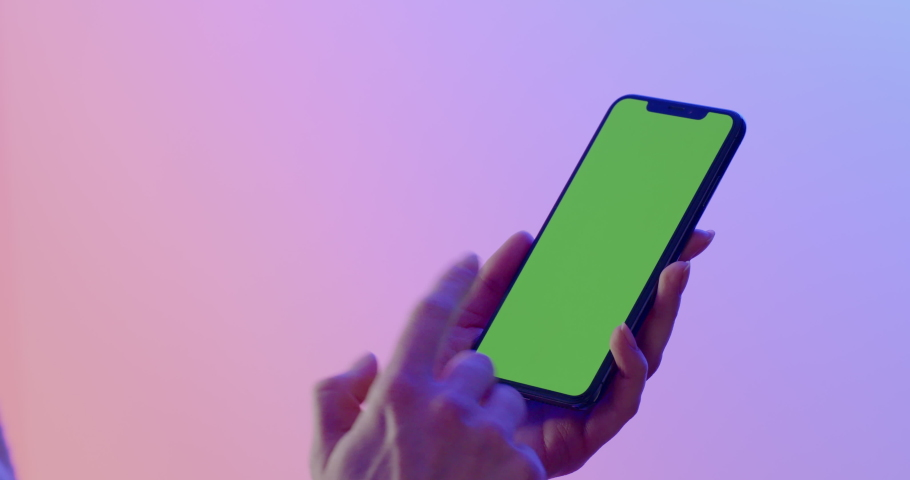 MINSK/BELARUS - CIRCA 2019: GREEN SCREEN CU Caucasian female using iPhone XS Max, vertical orientation, colorful neon background. 4K UHD RAW Graded footage