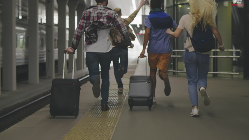 Back view of four friends passengers running along train platform being late. Tourist group missing train and trying to chase it. Four people running after train. Royalty-Free Stock Footage #1042707652