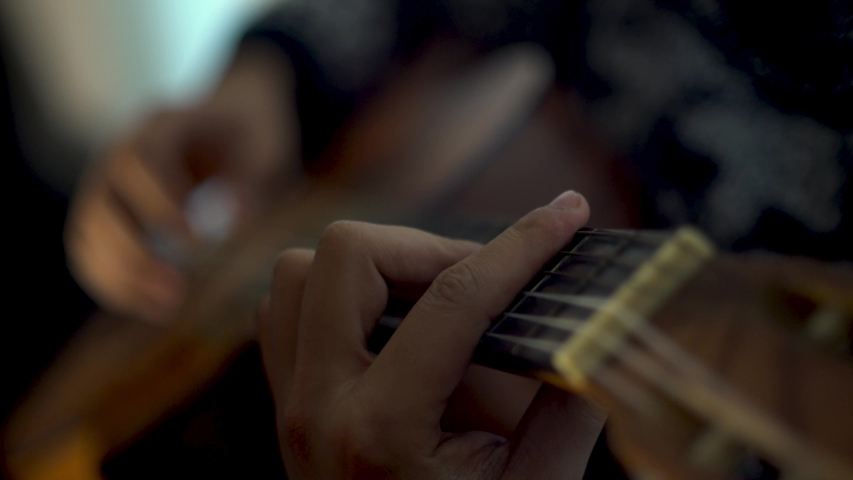 Young man plays guitar at home. Plays his new music. | Shutterstock HD Video #1042719835