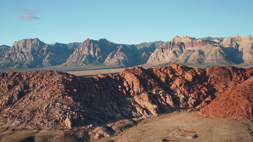 Aerial scenic shot of Calico Basin sandstone ridge and Red Rock Canyon mountains | Shutterstock HD Video #1042747528