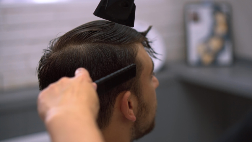 Client during beard shaving in barber shop. Hairdressing services. man cuts hair at a hairdresser-stylist in barbershop. scissors comb close-up Details of trimming. Cropped closeup  barber trimming | Shutterstock HD Video #1042753198