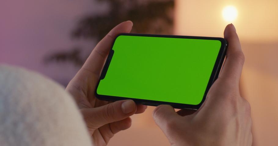 MINSK/BELARUS - CIRCA 2019: GREEN SCREEN CU Caucasian female using iPhone XS Max, horizontal orientation, modern apartment interior background. 4K UHD RAW Graded footage