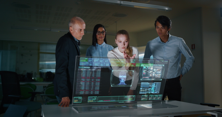 The modern designers are using a futuristic sophisticated technology screen with augmented reality holograms for a new project realization in an office. Hi-tech concept and future