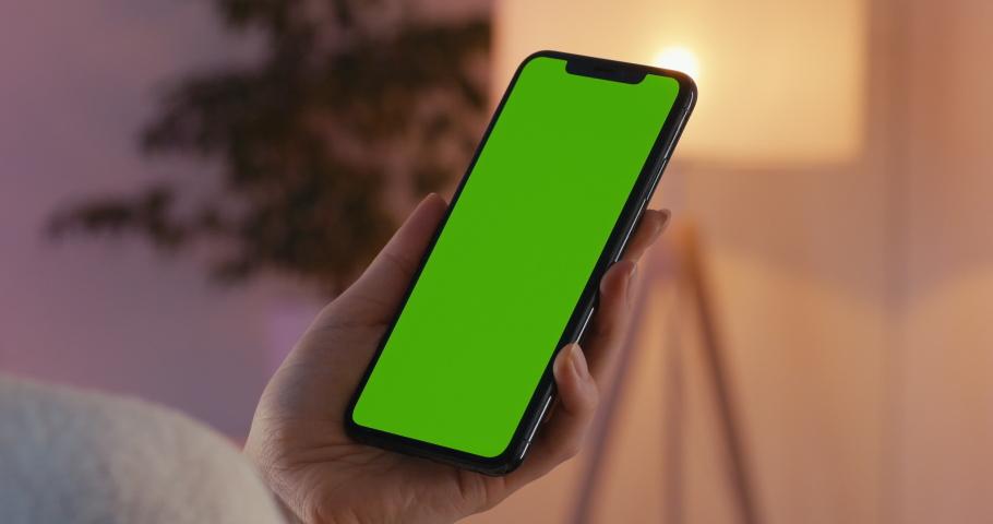 MINSK/BELARUS - CIRCA 2019: GREEN SCREEN CU Caucasian female using iPhone XS Max, vertical orientation, modern apartment interior background. 4K UHD RAW Graded footage