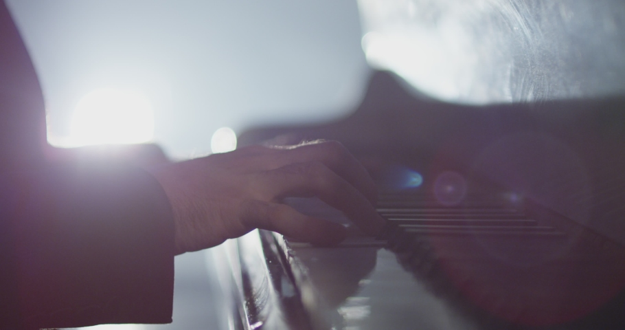 4K Footage of male hands playing grand piano . Man touches fingers on keys . Pianist plays in beautiful grand piano on stage in concert . Close up . Shot on ARRI ALEXA movie camera in slow motion . | Shutterstock HD Video #1042762363