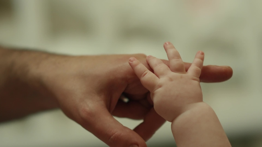 Close-up shot of baby's little cute hand reaching for father's loving finger . Baby holding parent's finger . Parent holding newborns hand in Slow Motion . Hand in hand. Father and his newborn baby . | Shutterstock HD Video #1042763212