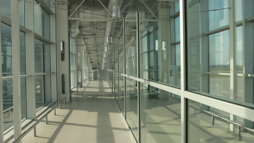 Stylish glass corridor in airport terminal to runway with planes. Transparent panoramic windows with amazing view on airfield. Empty path, escalator on right. Royalty-Free Stock Footage #1042763605
