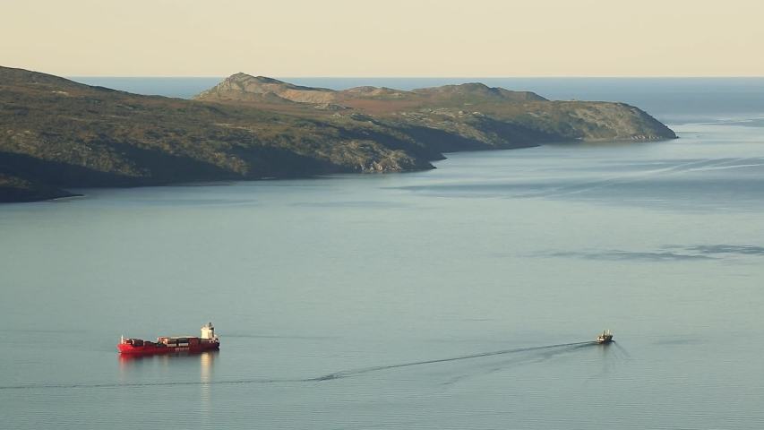 Beautiful seascape with bay and cape. Cargo ship on the roadstead and a vessel. Aerial view of the Staritsky Peninsula and the Sea of ​​Okhotsk. Nagaev Bay, Magadan Region, Far East Russia. Timelapse.