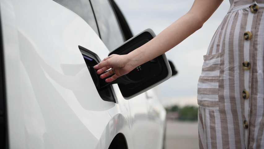 Woman plugs in charger into socket of her modern new electric car.