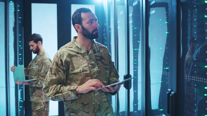 Caucasian soldier of special forces inspecting modern datacenter secure storage. Cyber security worker in uniform cooperating on mission inside server room of database. Royalty-Free Stock Footage #1042771894