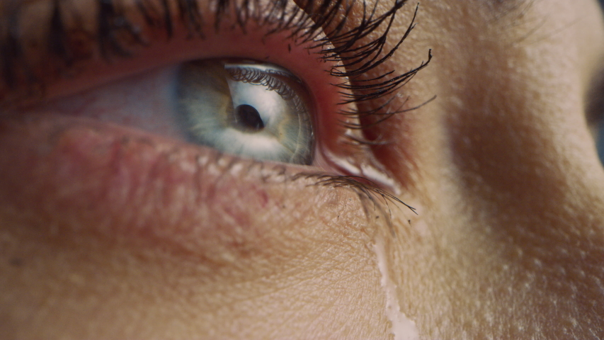 Close Up Macro Zoom Shot of a Crying Eye. Young Beatiful Female with Natural Light Blue, Yellow and Brown Color Pigmentation on the Iris. Mascara is Applied to Eyelashes. Tears are Flowing Down. | Shutterstock HD Video #1042774627