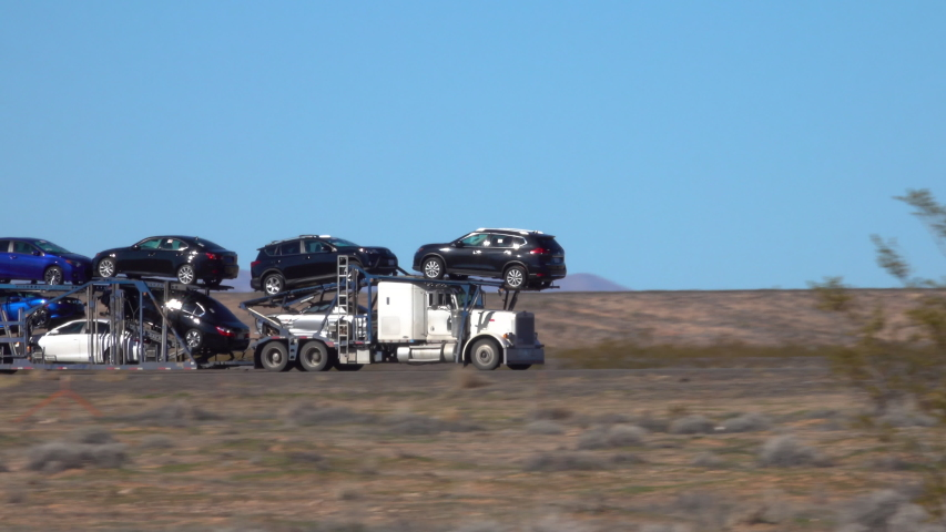 CLOSE UP Freight truck hauls cars down a highway crossing the Utah desert. Cargo lorry speeds along the interstate freeway while transporting brand new cars across the country. Hauling cars across USA