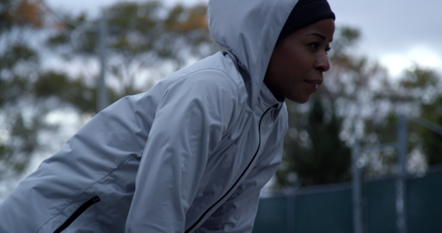 Runner in hooded running jacket leaning over after hard run breathing heavily, out of breath