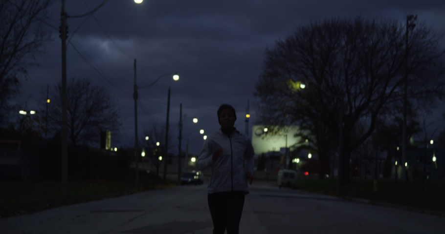 Jogger running at night in slow motion in fitness attire on empty street in industrial area of city towards camera | Shutterstock HD Video #1042803670