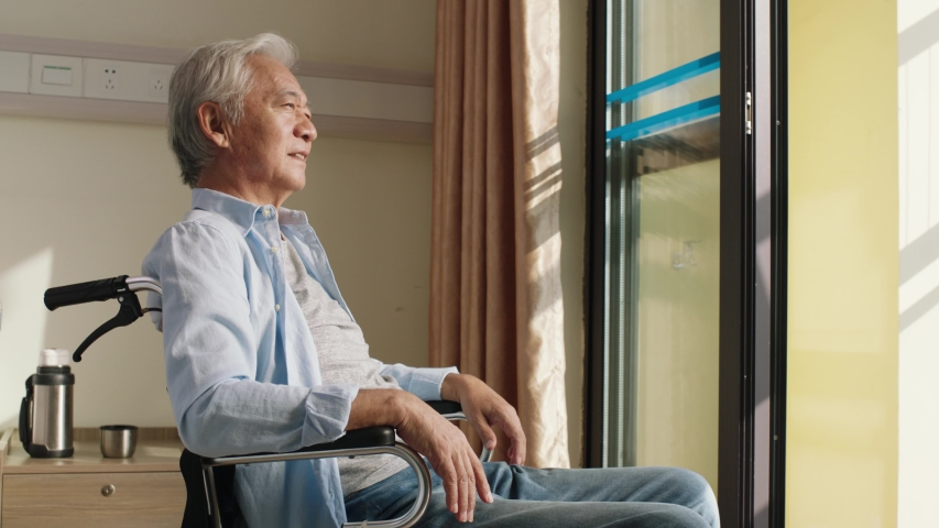 Asian old man sitting in wheel chair in his room in nursing home looking happy and content