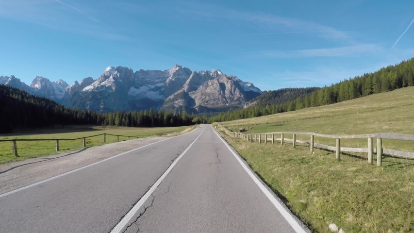 Driving on Italian alps with beautiful mountains on background. Empty road in Trentino, Italy, with green trees and meadows. Travel and transportation concepts   Shutterstock HD Video #1042817539
