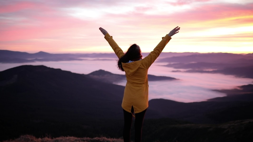 Young beautiful woman stands on top of a mountain and raises her hands up to meet the sunset. Hiker woman standing with hands up achieving the top and enjoys incredible mountain landscape   Shutterstock HD Video #1042830328