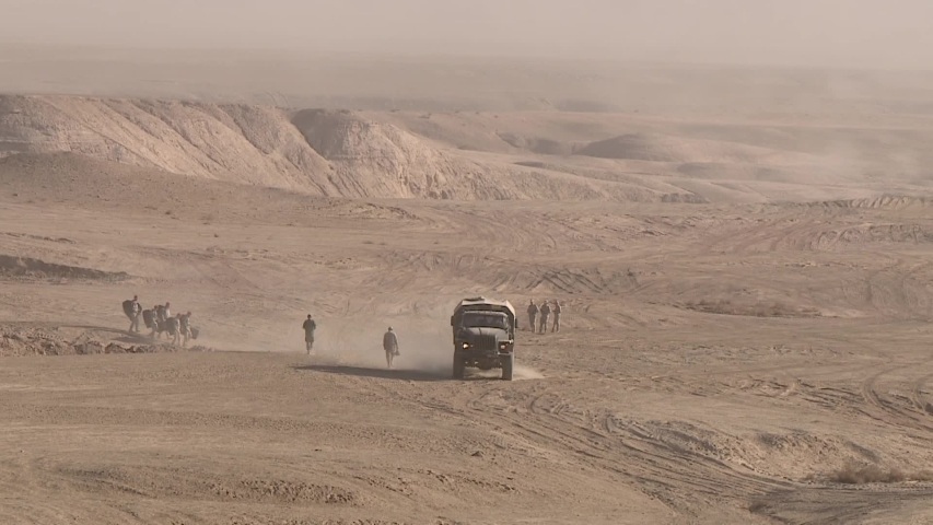 Military soldiers moving through the desert, driving a truck, raising clouds of dust.