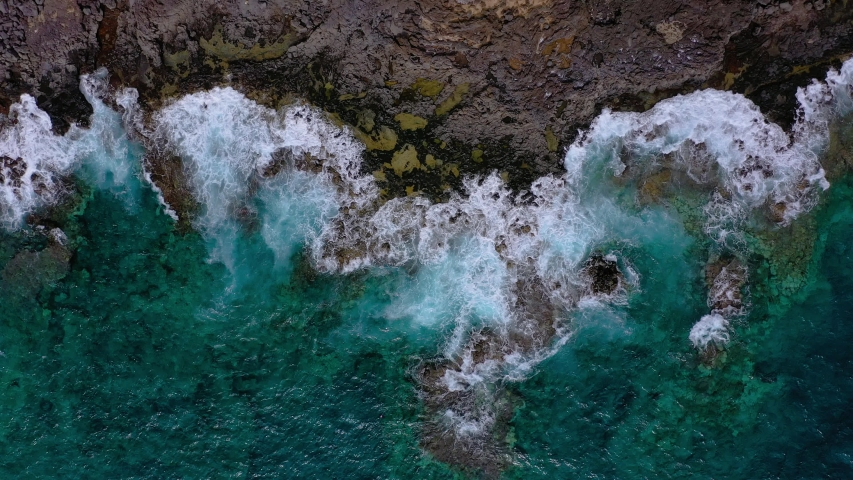 Top view of a deserted coast. Rocky shore of the island of Tenerife. Aerial drone footage of ocean waves reaching shore