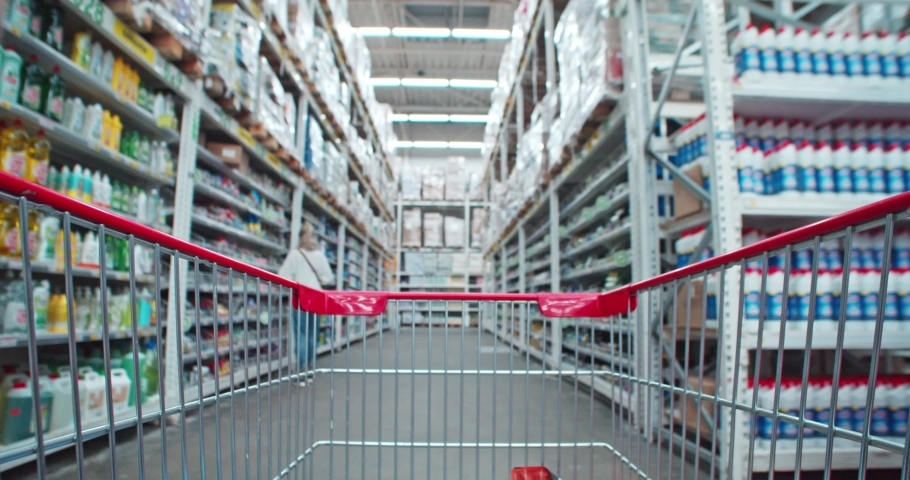 View from empty store trolley of young woman putting shopping items inside. Pov moving a shopping cart through supermarket household aisle. Close-up. Royalty-Free Stock Footage #1042848073