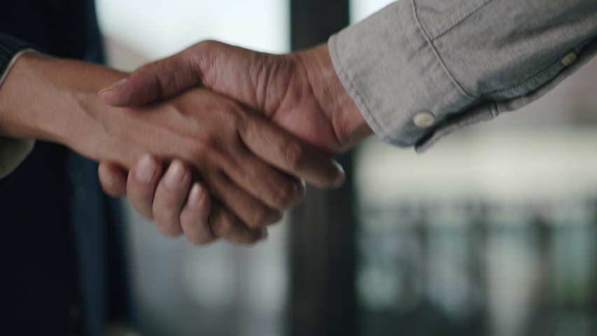Close up. Hand of two Asian business people gathered to handshake agree to a deal or say hello in the office