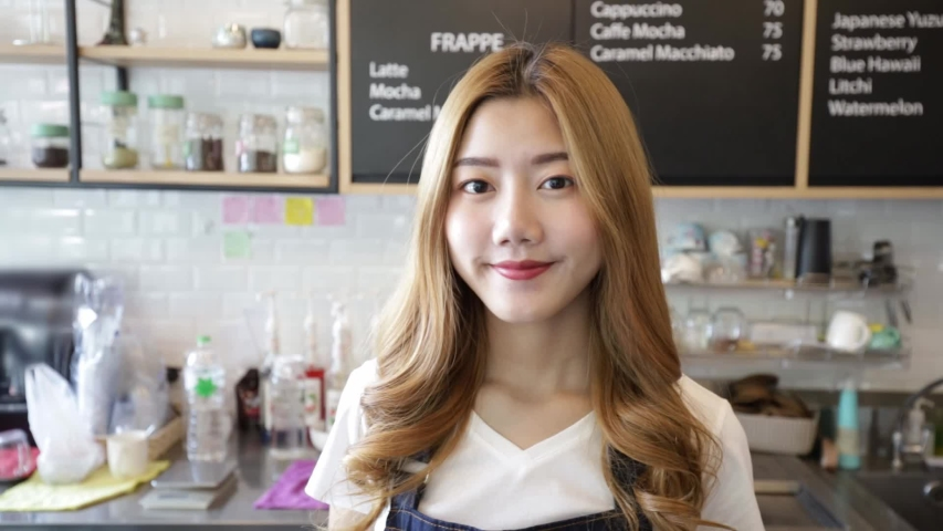 Beautiful Smiling AsianWoman in blouse dancing, smiling and looking at camera in cafe. Owner Young Entrepreneur Passion .Small business owner Korean girl in apron relax toothy smile looking.
