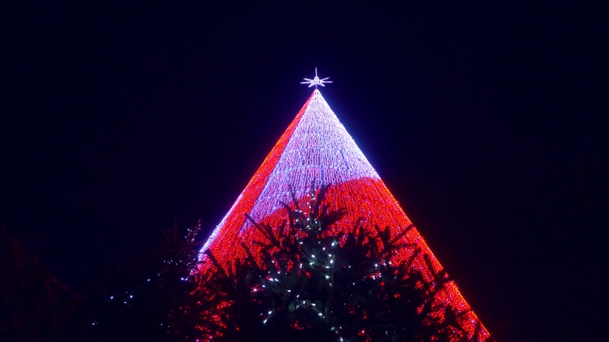A modern Christmas tree made of thousands of colorful light bulbs in the central square of the Duomo in Milan. A star on top of a Christmas tree. Night illumination for the holidays. New Year. Street  | Shutterstock HD Video #1042877098
