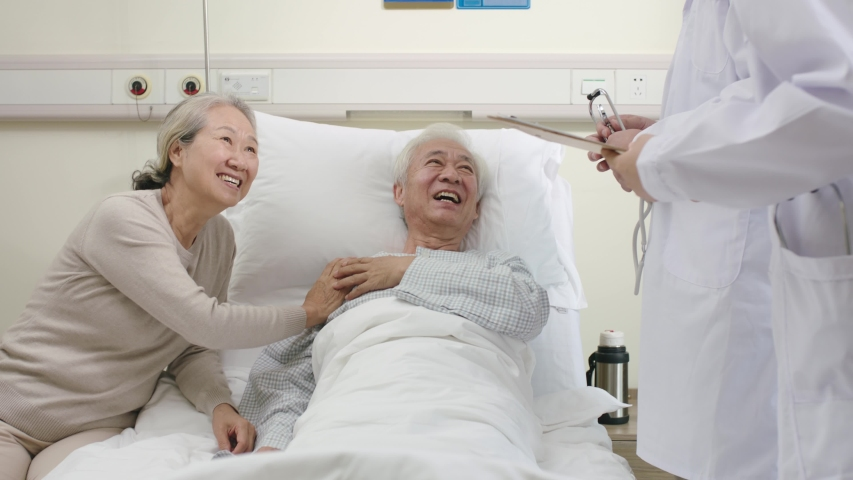 two young asian doctors making rounds talking to senior patient in hospital ward