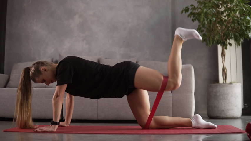 Resistance band fitness girl in black sportswear doing leg workout floor exercises with rubber strap elastic. Glute muscle activation with kickback for cellulite. Lifting legs with rubber band. Royalty-Free Stock Footage #1042879741