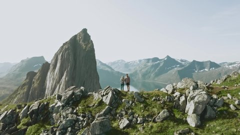Family couple with baby traveling hiking in Norway Segla mountain aerial view adventure healthy lifestyle summer vacations activity Senja islands