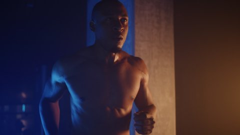 African-American athlete running on treadmill, muscular built, listening to music while training in gym, dramatic lightning, shot on Red Weapon Helium