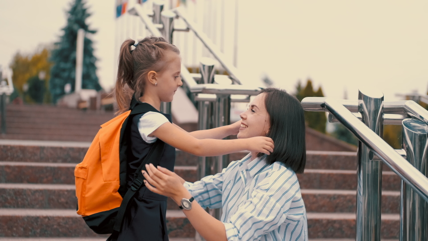 European mother and daughter are hugging each other after school. The mother is cradling her daughter's head and smiling.